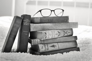 a stack of books topped with a pair of glasses